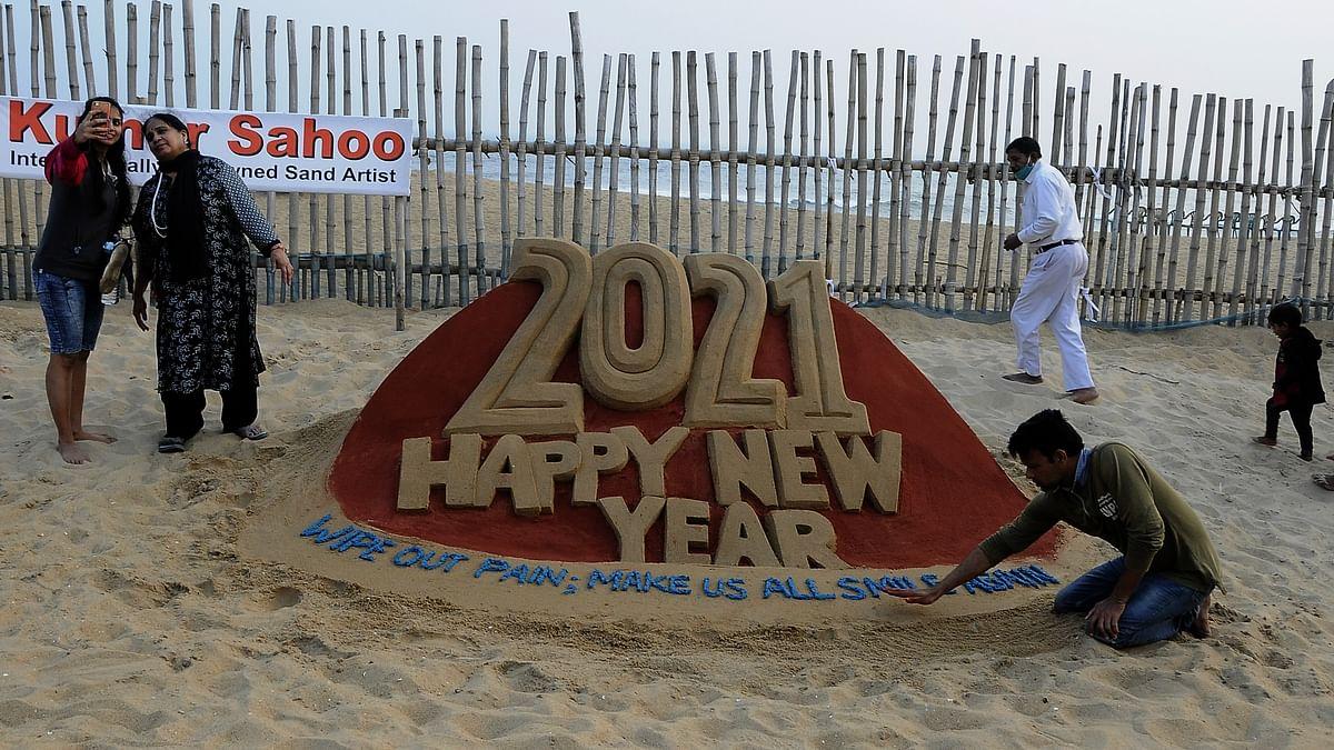 اوڈیشہ میں ساحل سمندر پر نئے سال کے موقع پر ریت سے فن پارہ تیار کرتے سینڈ آرٹسٹ / Getty Images