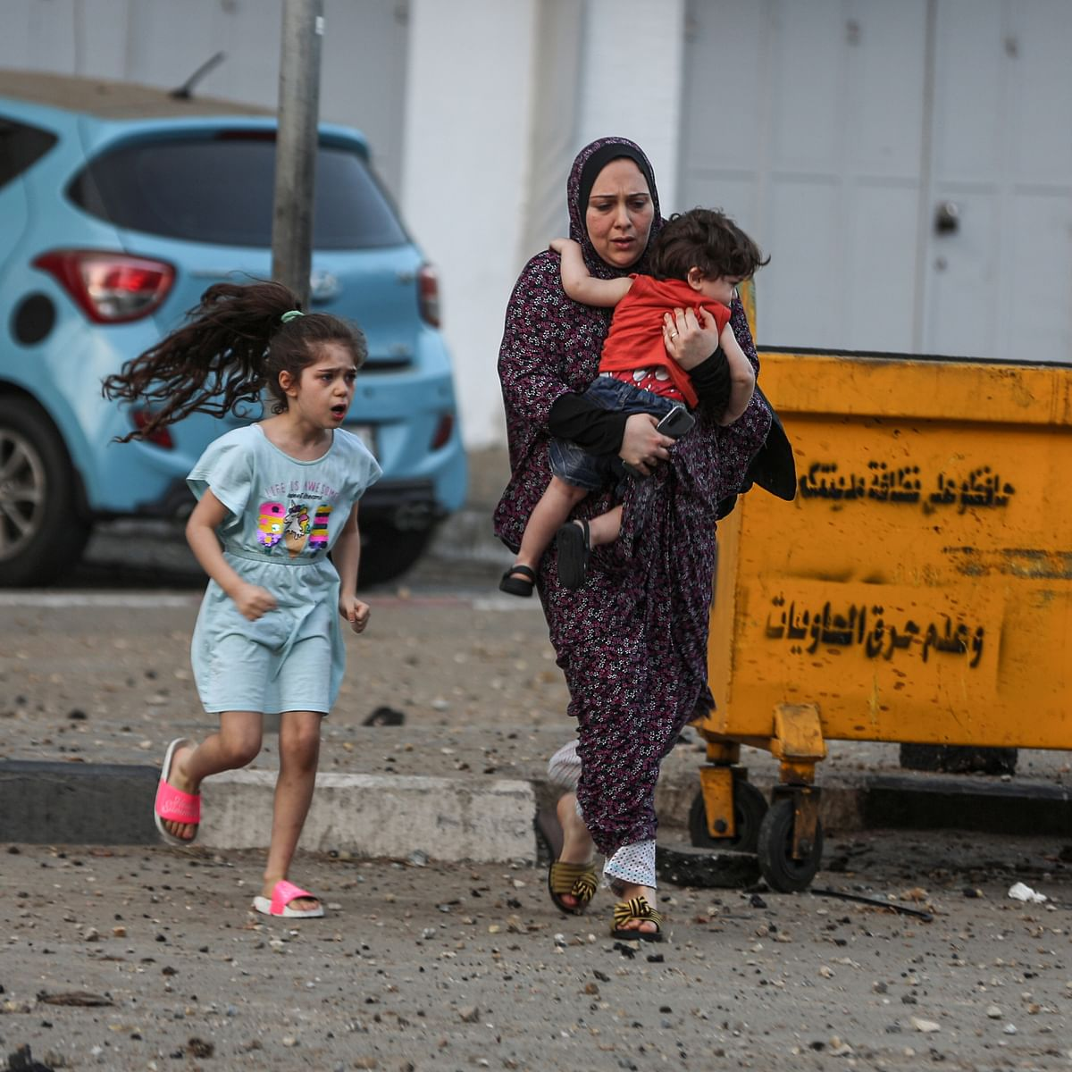 بدحواس حالت میں فلسطینی خاتون اپنے بچوں کی حفاظت کی کوشش کرتے ہوئے / Getty Images