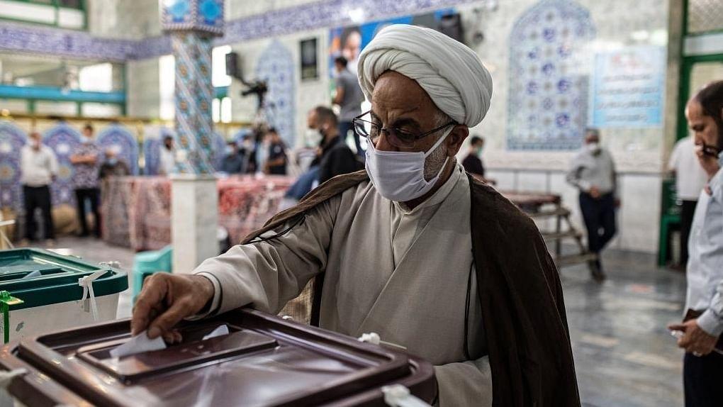 ایرانی صدارتی انتخابات میں ووٹ ڈالتے ہوئے ایک شخص تصویر آئی اے این ایس