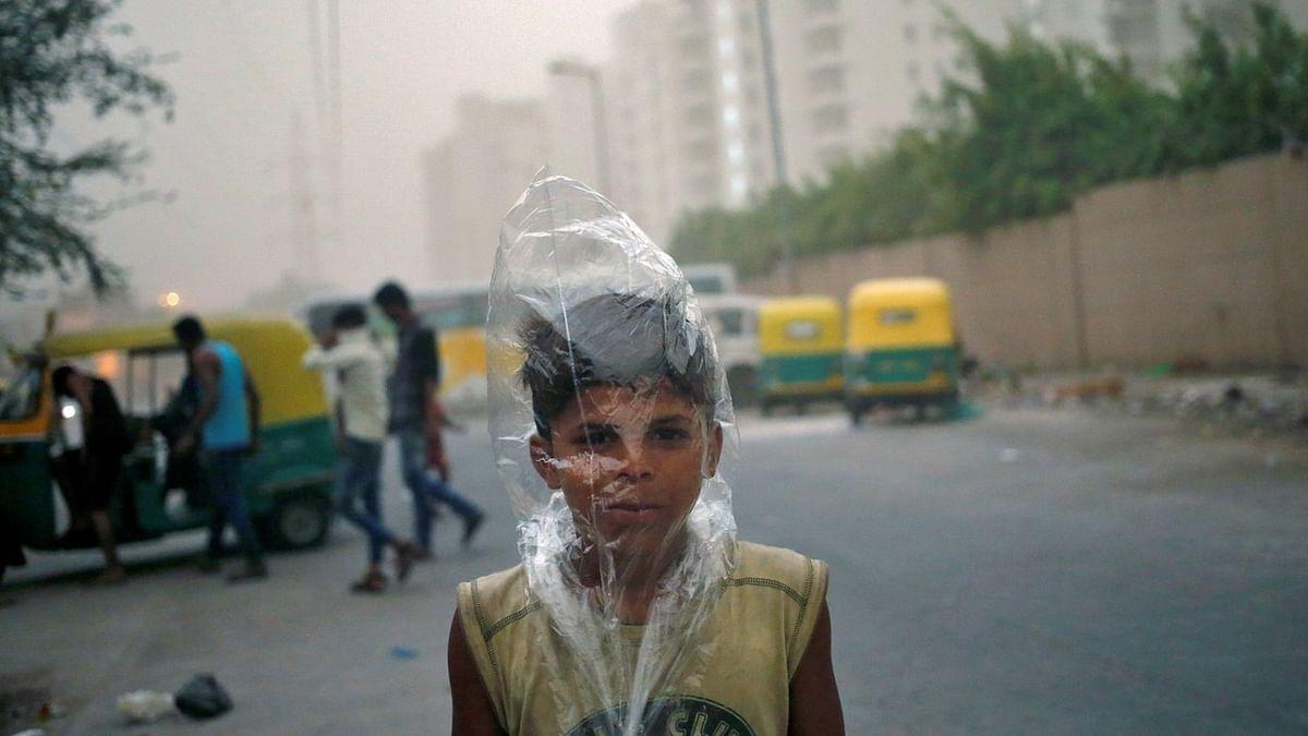 नई दिल्ली में धूल भरी आंधी से बचने के लिए एक बच्चा सिर पर पॉलिथीन बैग लगाए घूम रहा है. (Photo: Reuters/Anindito Mukherjee)