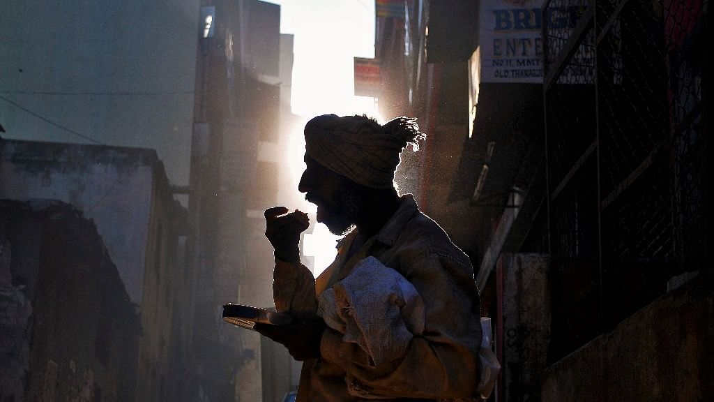 बेंगलुरु में एक बेघर आदमी सड़क किनारे अपनी भूख मिटाता हुआ. (फोटो: Reuters/अभिषेक एन चिनप्पा)