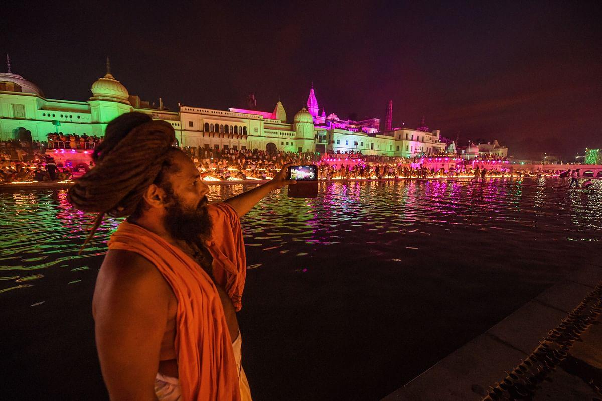 दीपोत्सव समारोह में सरयू नदी के तट पर सेल्फी लेता एक साधु