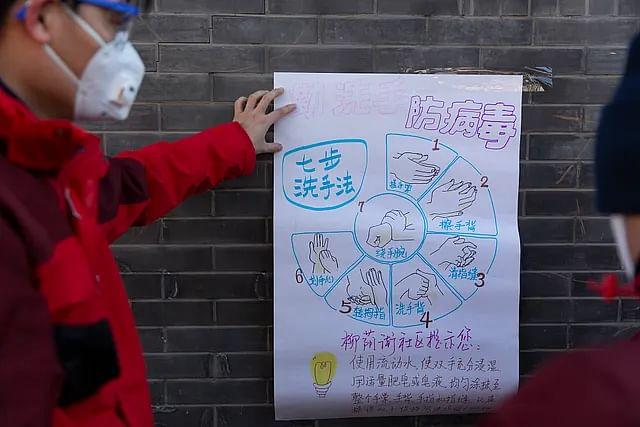 बीजिंग में सड़क किनारे दीवार पर एक सामुदायिक कार्यकर्ता अपने हाथ से पोस्टर बनाकर दीवार पर चस्पां करता है कि कैसे सही तरीके से हाथो को धोया जाए ताकि वायरस को फैलने से रोका जा सके.