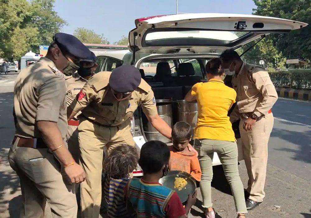 कर्फ्यू के दौरान सड़कों पर रहने वालों को पुलिस ने बांटा भोजन