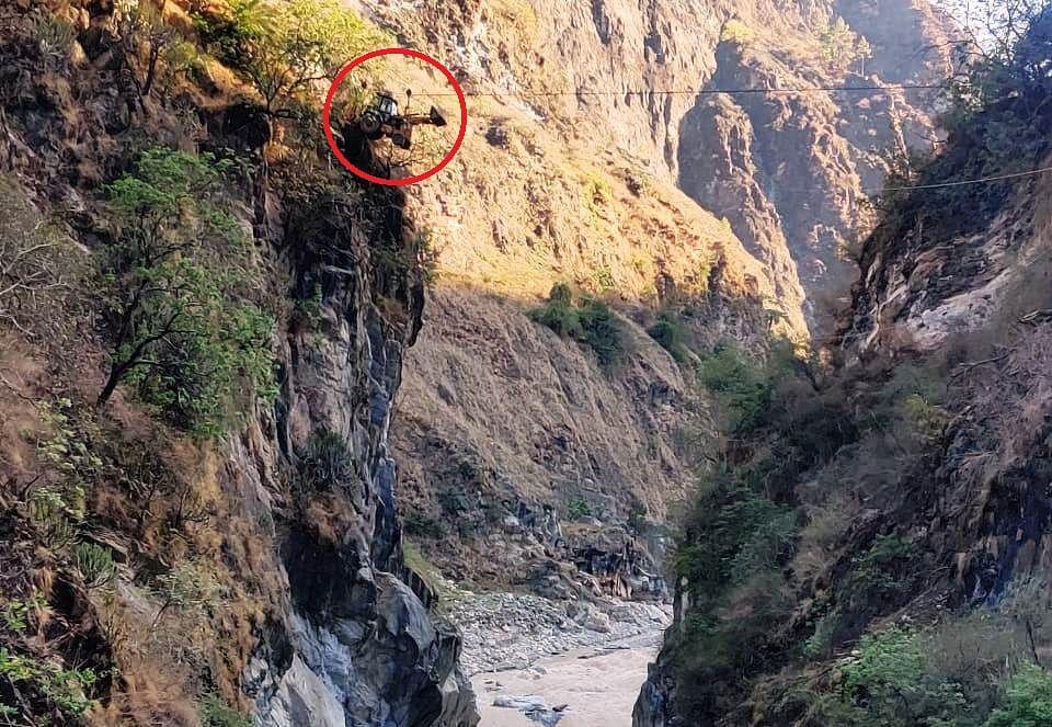 चेन कुप्पी के सहारे हवा में अलकनंदा नदी के एक छोर से दूसरे छोर पहुंचाई जेसीबी