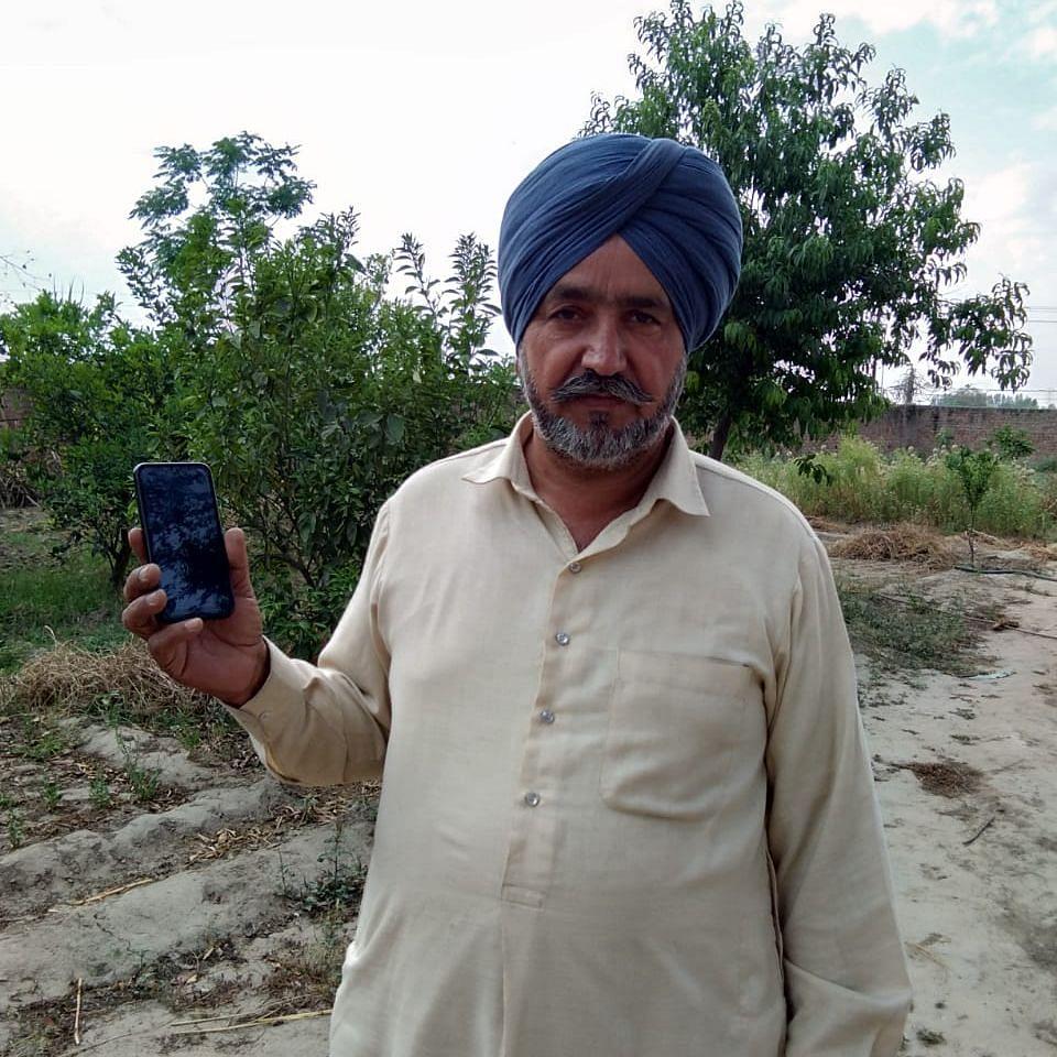 चित्र परिचय: मोबाइल पर गेहूं की सीधी खरीद के लिए भुगतान की रसीद दिखाते किसान।