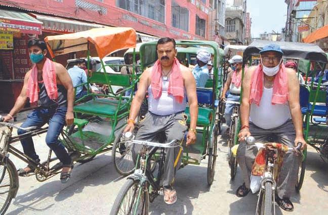 व्यापारियों ने रिक्शा चलाकर किया विरोध