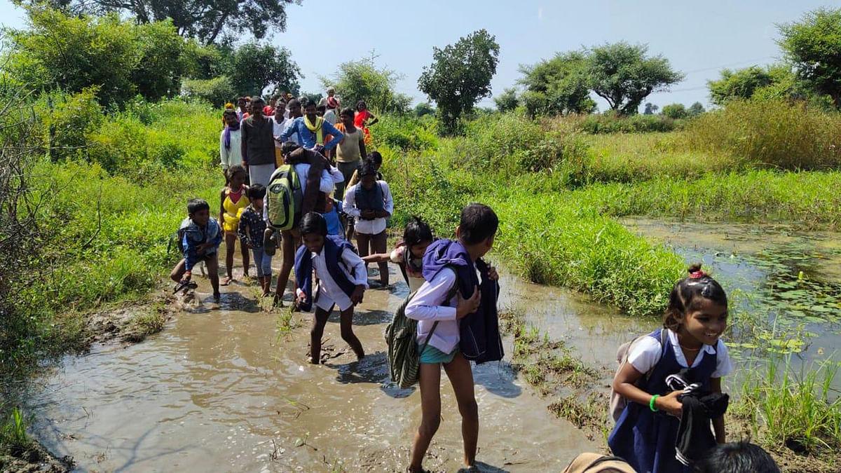 छतरपुरः बच्चों को कंधे पर बैठाकर स्कूल पहुंचा रहे अभिभावक