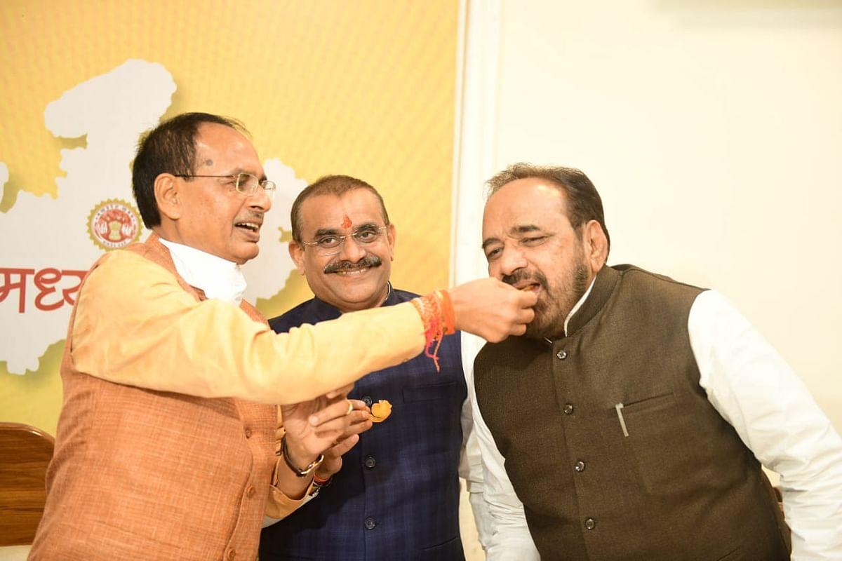 सीएम शिवराज सिंह चौहान मंत्री गोपाल भार्गव को मिठाई खिलाते