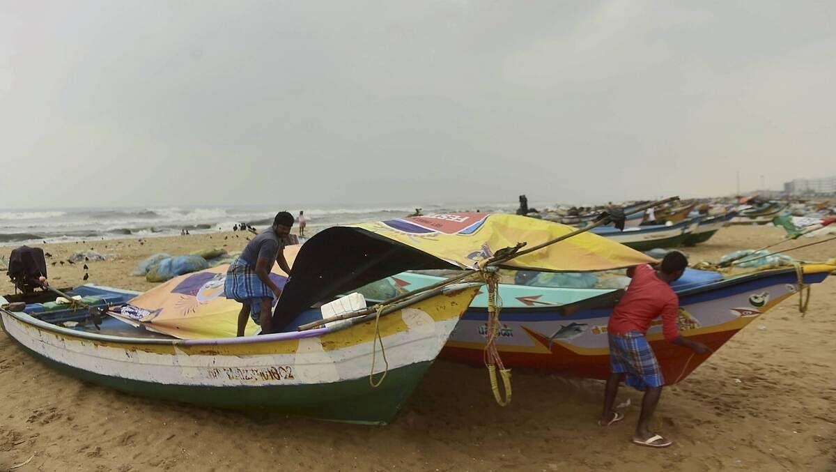 मछुआरे अपनी नावों को चेन्नई बीच पर ढंकते हुए