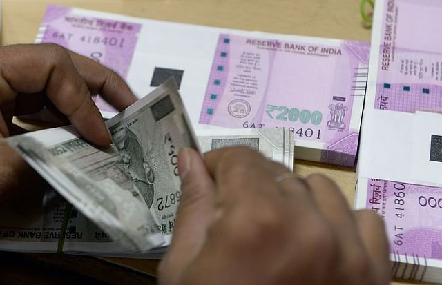 A bank staff member counts Rs 500 notes to give to customers. (INDRANIL MUKHERJEE/AFP/Getty Images)