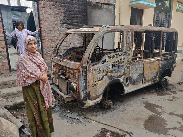 Asmana Jabeen shows her husband's burnt vehicle.
