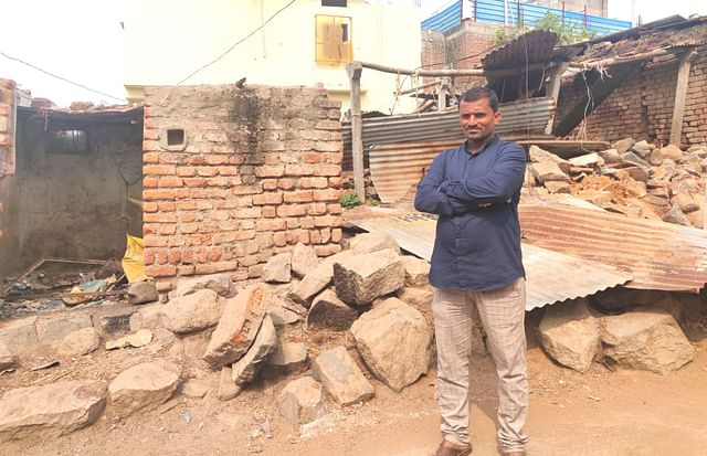 Raju from Korbagalli stands in front of his fire-ravaged house.