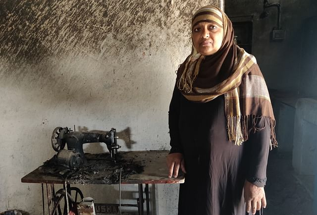 Afsari Begum With her burnt sewing machine.