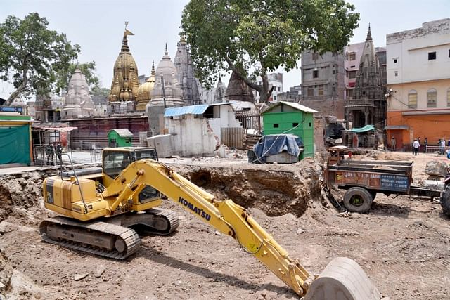 Demolition work on at the site with the Kashi Vishwanath temple in the background