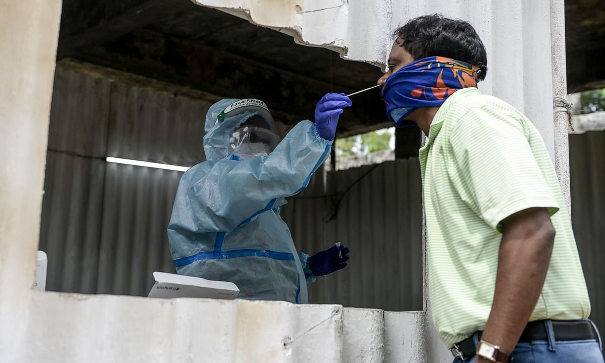 A health worker wearing personal protective equipment (PPE) collects a swab sample for COVID-19 test