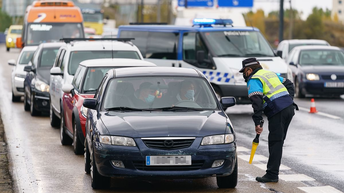 A policeman controls a car at a checkpoint on the highway in Burgos, northern Spain