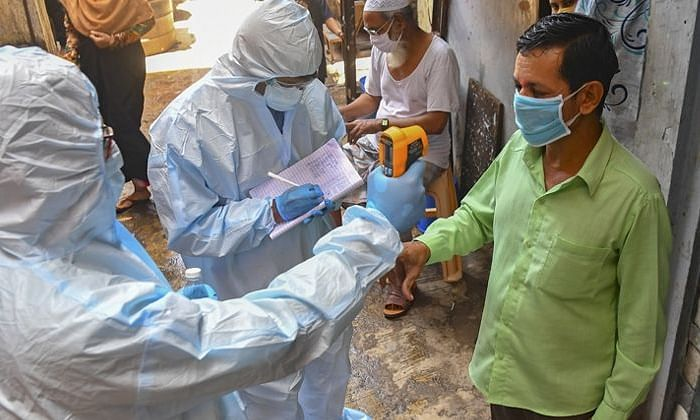 Health workers checking the temperature during the screening for COVID-19 (file photo)