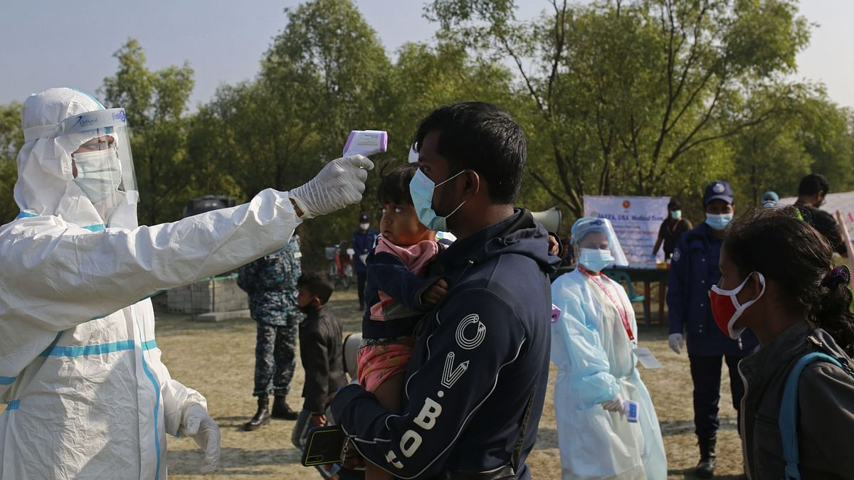 An official wearing a protective suit checks the body temperature of a man