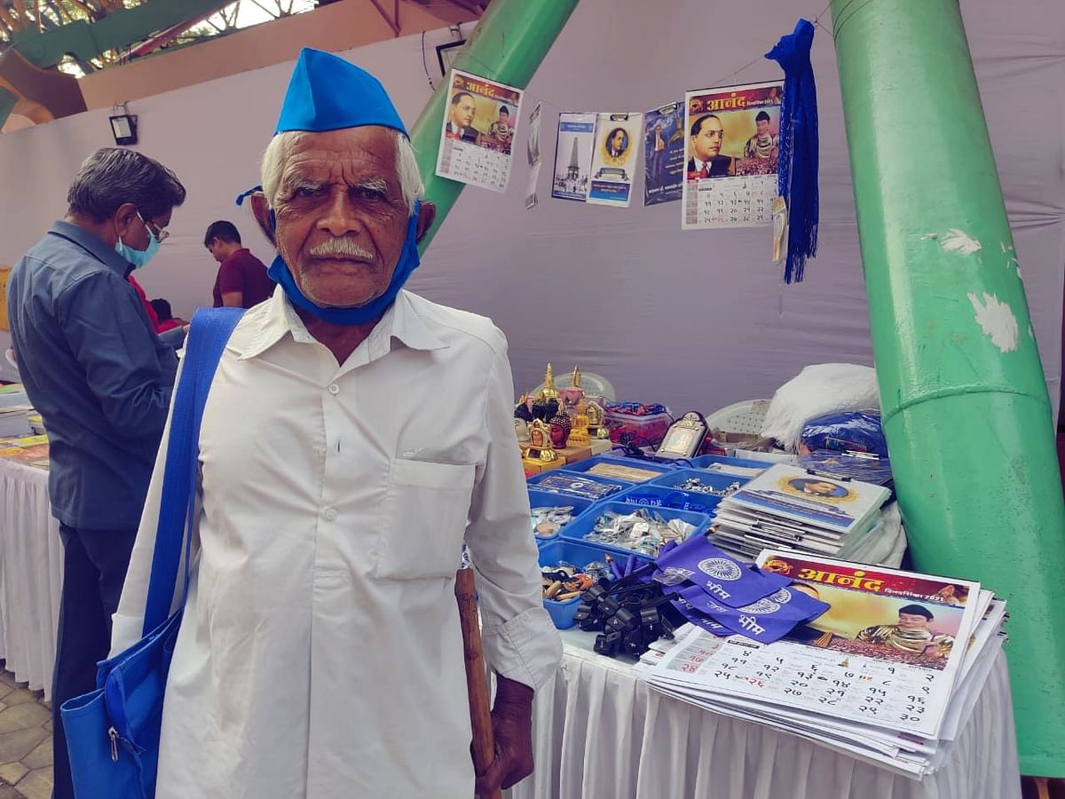 Thackrji Gaikwad, 80-year-old farmer, standing at a book stall at the Elgar Parishad event in Pune