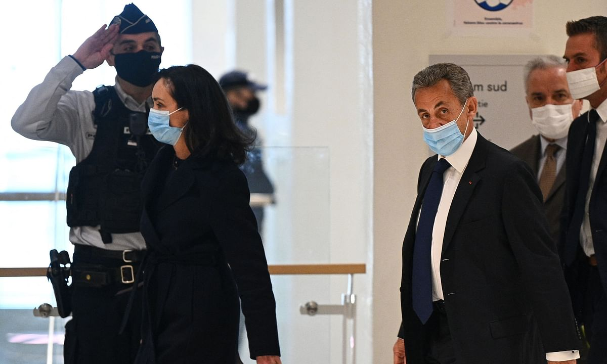 An officer salutes as the former French president Nicolas Sarkozy (R) arrives at the Paris court house to hear the final verdict in a corruption trial in Paris on March 1, 2021.