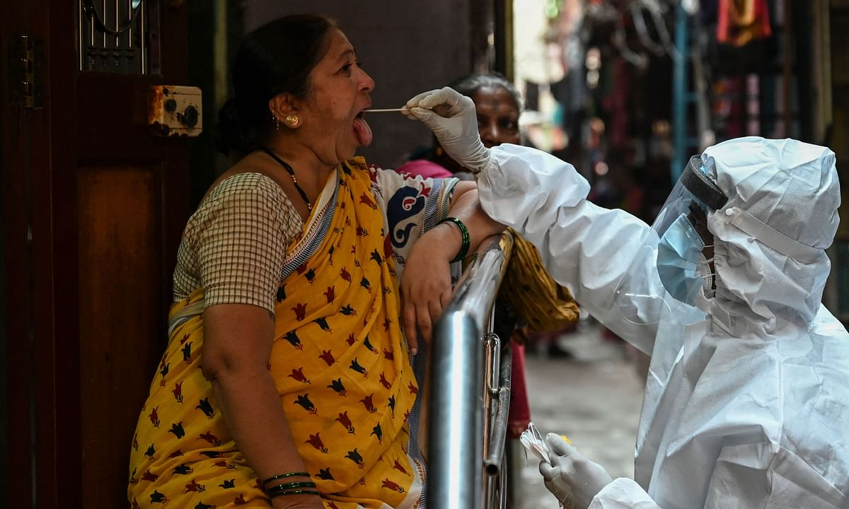 A health worker  takes a swab sample of a resident for a COVID-19 test at Dharavi slum in Mumbai