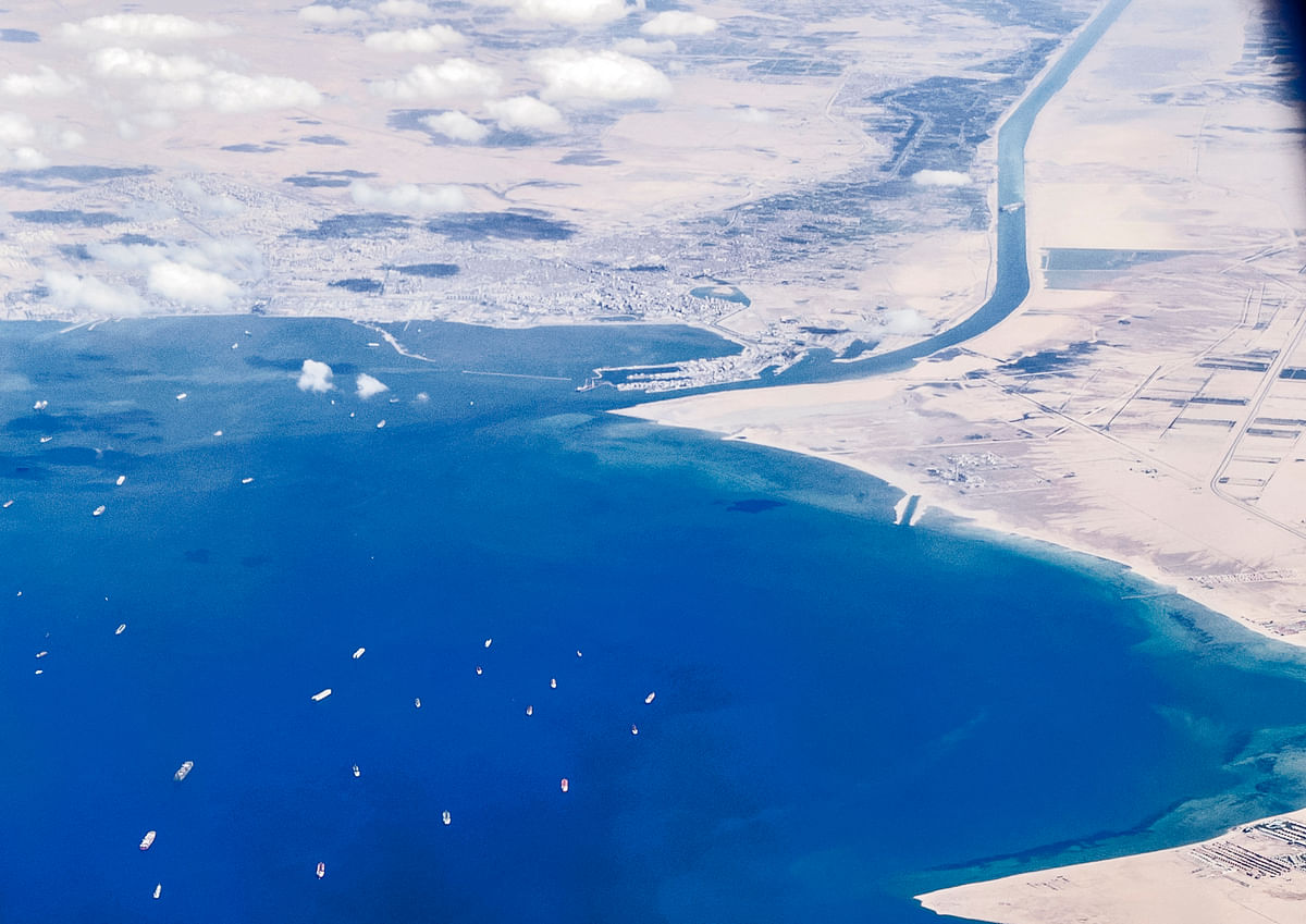 An aerial view taken on March 27, 2021 from the porthole of a commercial plane shows stranded ships waiting in queue in the Gulf of Suez to cross the Suez Canal at its southern entrance near the Red Sea port city of Suez.