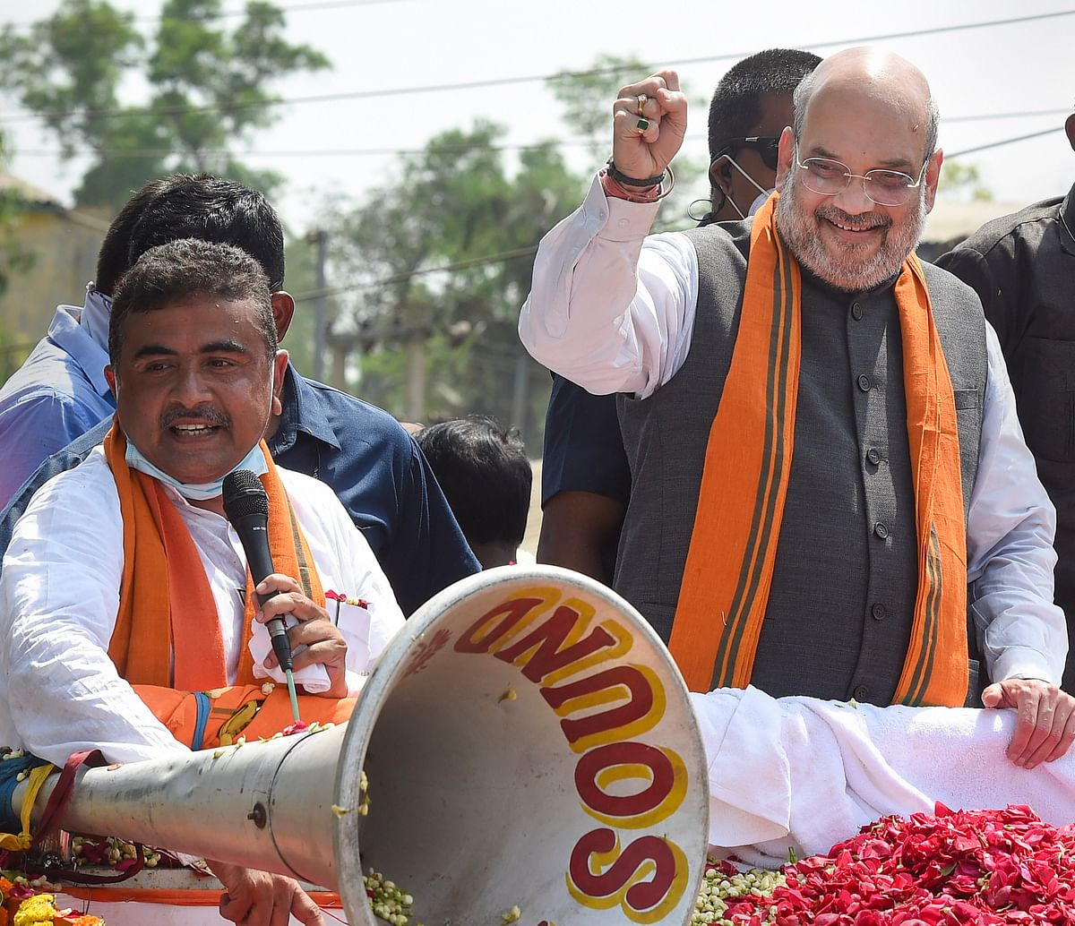 Union Home Minister Amit Shah during a road show in support of BJP candidate Suvendu Adhikari (L) from Nandigram Constituency for the Assembly elections, in Nandigram, Tuesday, March 30, 2021