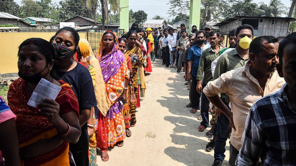 Voters wait in queue to cast their ballots during Phase 1 of Assam's legislative election in Koliabor, some 186 km from Guwahati on March 27, 2021.