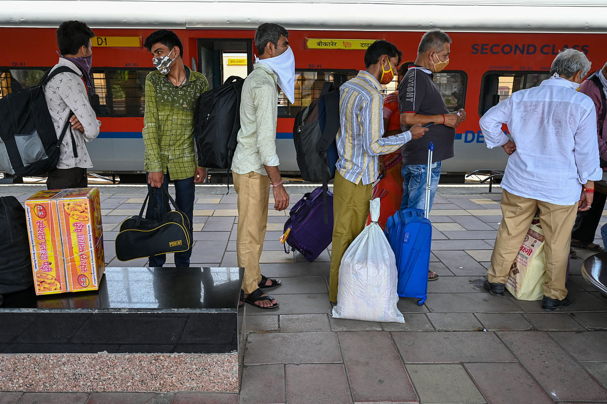 Passengers stand in a queue outside Lokmanya Tilak Terminus to catch a train back home ahead of the harvest season, in Mumbai amidst rising COVID-19 cases