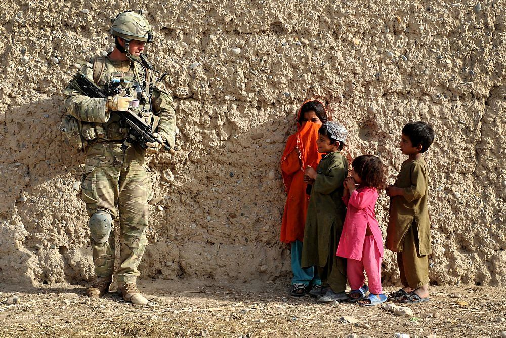 Soldier talks to children while on patrol in Afghanistan.