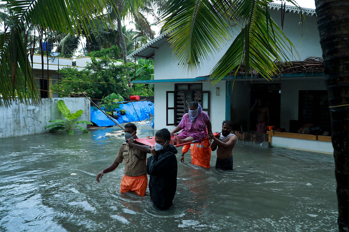 Police and rescue personnel evacuate local residents from a flooded house in a coastal area after heavy rains under the influence of cyclone Tauktae in Kochi