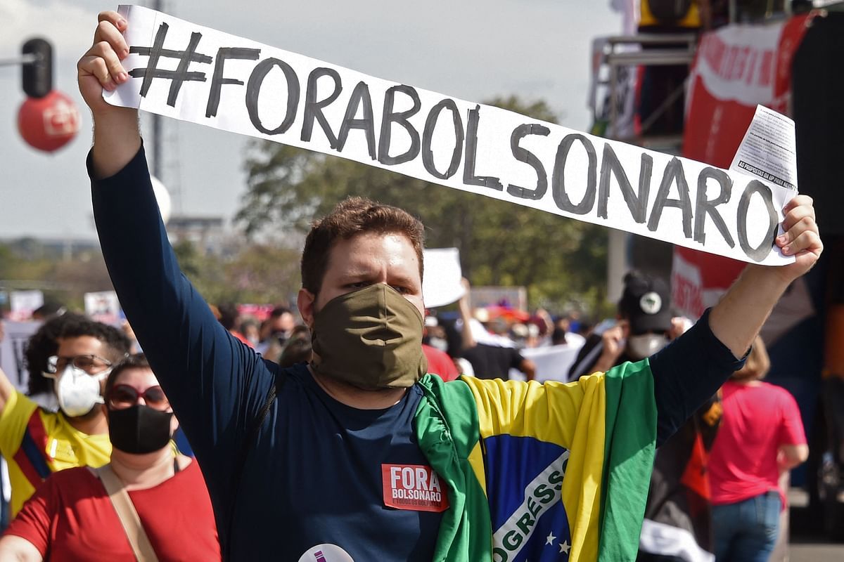 A demonstrator holds a banner reading Bolsonaro out, referring to Brazilian President Jair Bolsonaro during a protest against his handling of the COVID-19 pandemic, in Brasilia, on May 29, 2021.