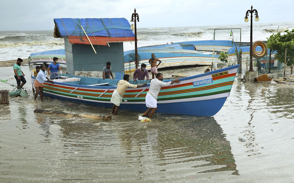 People remove fishing boats from the seashore ahead of cyclone Tauktae, at Baypore in Kozhikode, Friday, May 14, 2021.