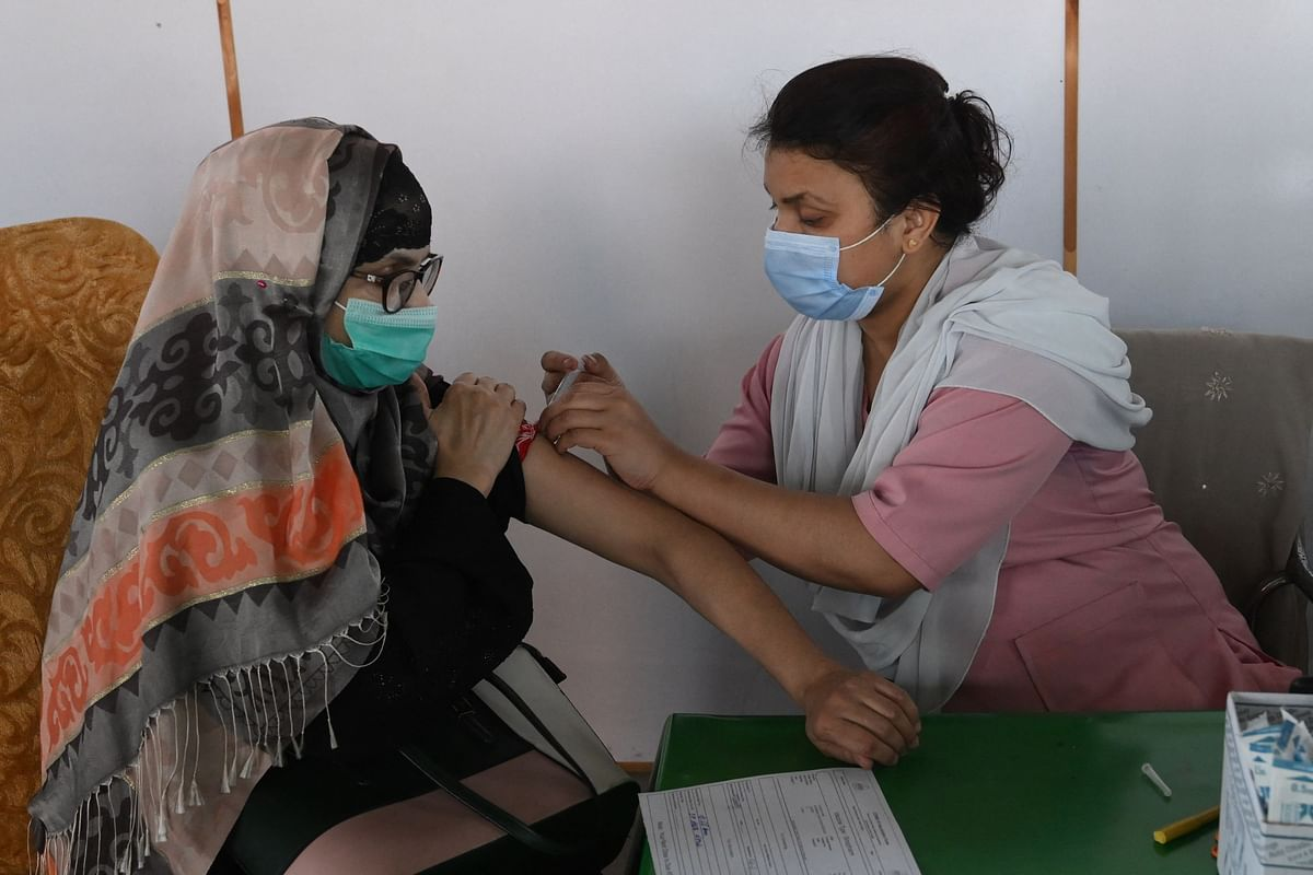 A health worker inoculates a woman with the Sinopharm Covid-19 coronavirus vaccine at a vaccination camp in Lahore on May 5, 2021.