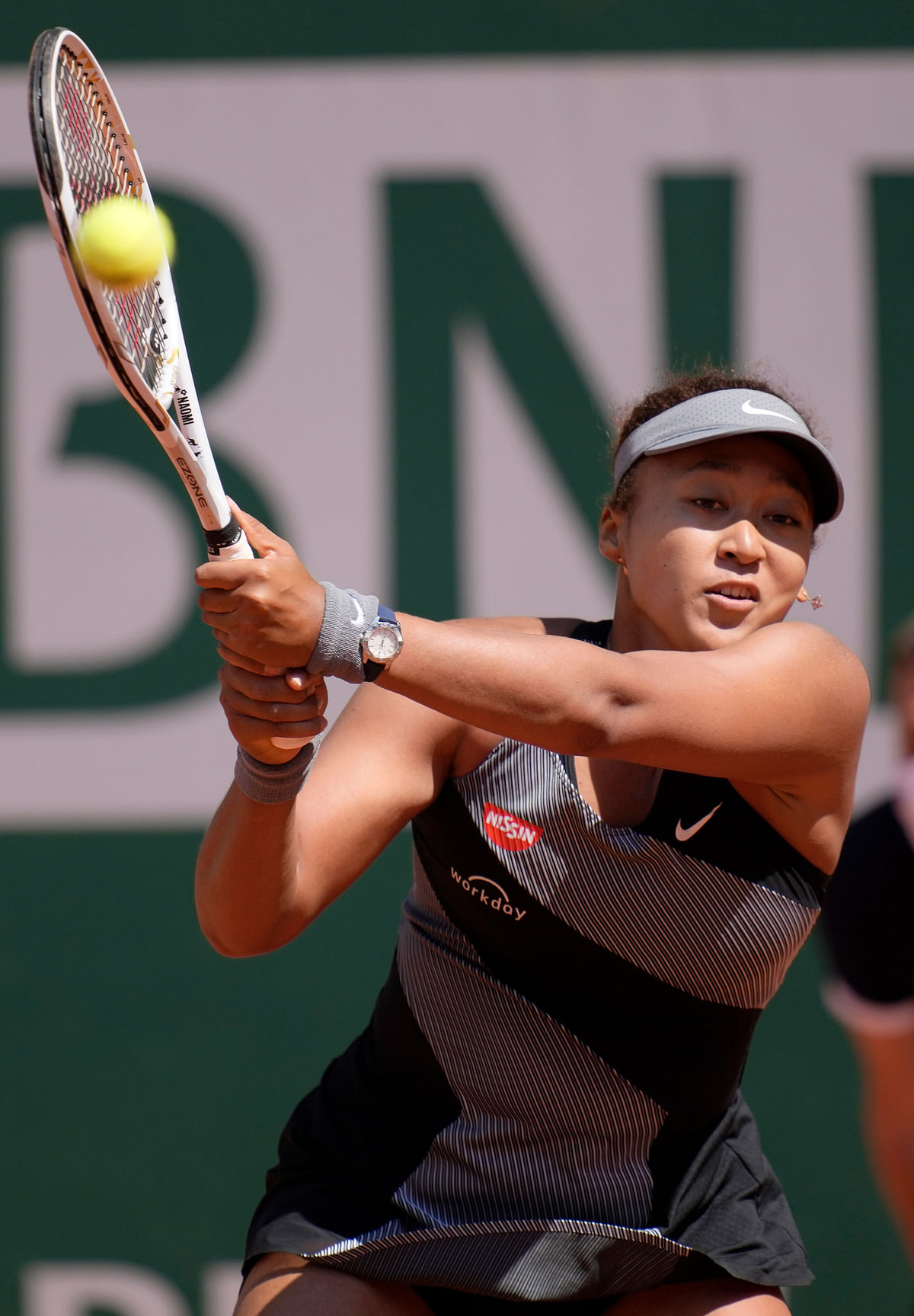 Naomi Osaka returns the ball to Romania's Patricia Maria Tig during their first round match of the French open tennis tournament at the Roland Garros stadium Sunday, May 30, 2021 in Paris.