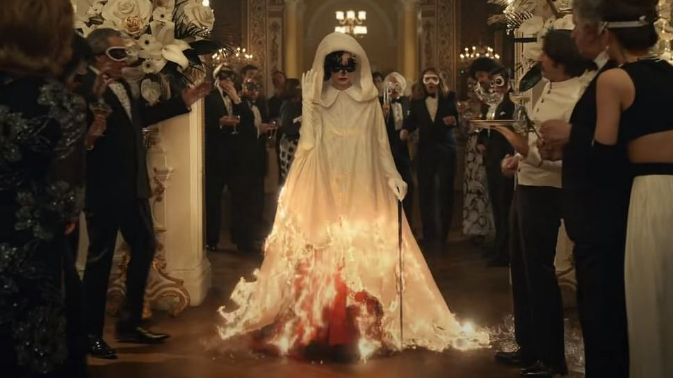 A screenshot from the film trailer of 'Cruella' featuring actor Emma Stone in a white robe and a red gown