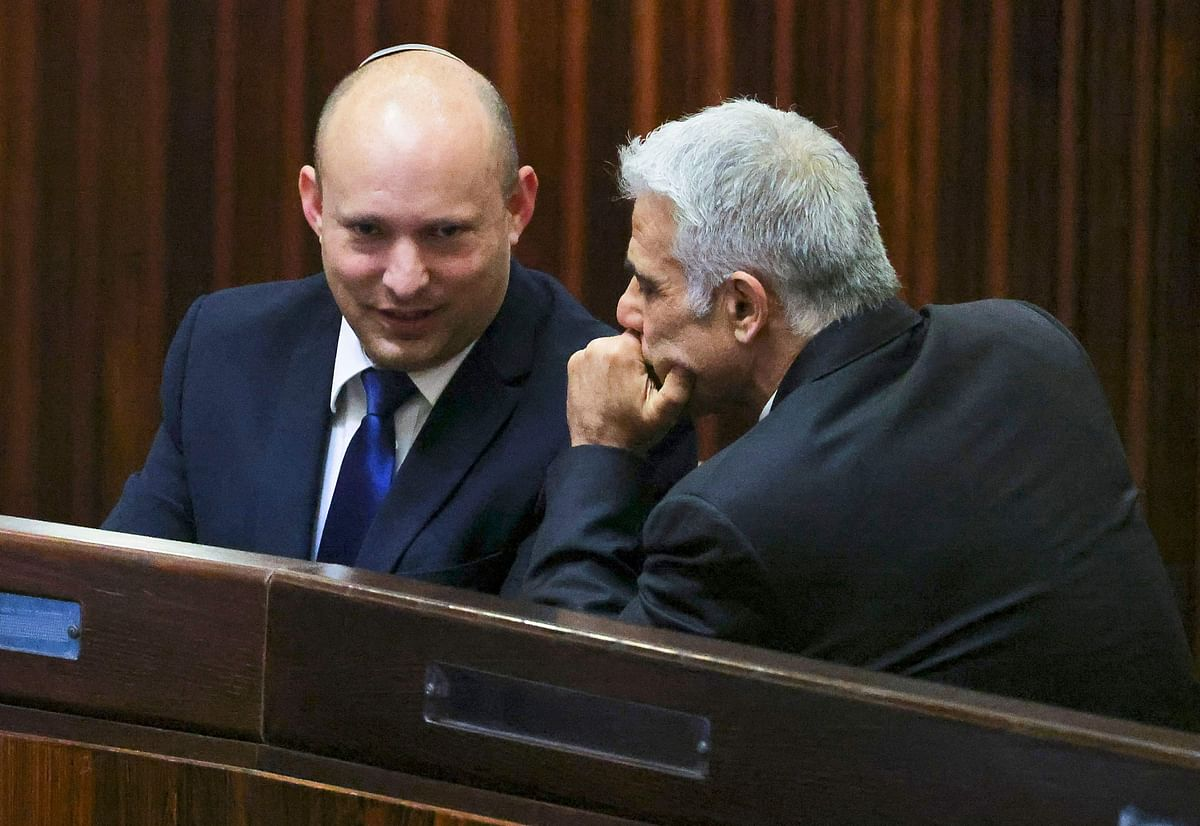 Israel's Yamina party leader, Naftali Bennett (L), smiles as he speaks to Yesh Atid party leader, Yair Lapid, during a special session of the Knesset, Israel's parliament, to elect a new president, in Jerusalem on June 2, 2021
