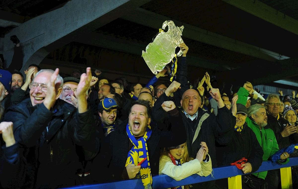 Excited fans cheering for AFC Wimbledon at crucial FA Cup match