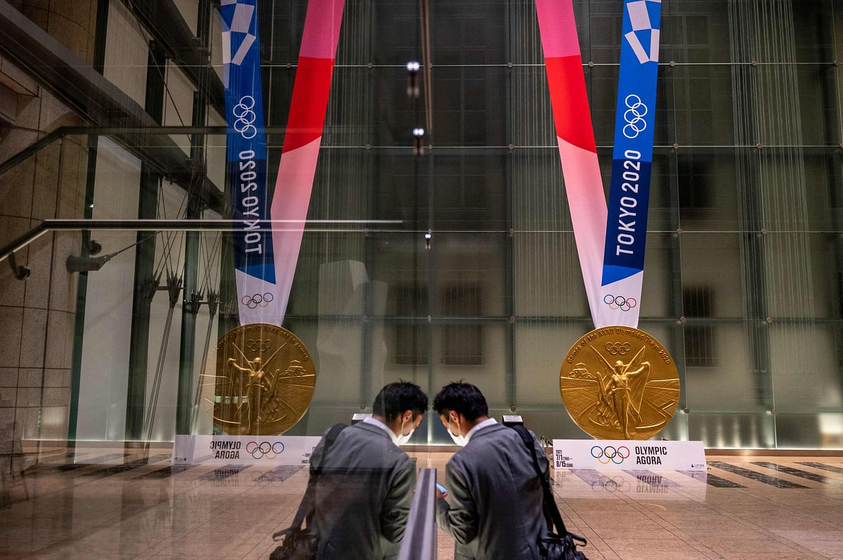A man walks near a large-scale reproduction of the Tokyo 2020 Olympic Games gold medal as part of the Olympic Agora event at Mitsui Tower in Tokyo