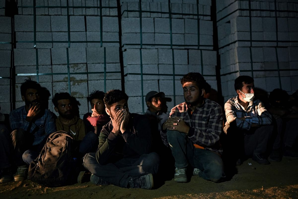 Afghan migrants rest while waiting for transport by smugglers after crossing the Iran-Turkish border on August 15, 2021 in Tatvan, on the western shores of Lake Van, eastern Turkey