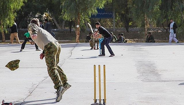 A team of U.S. Army soliders is playing  cricket with the locals