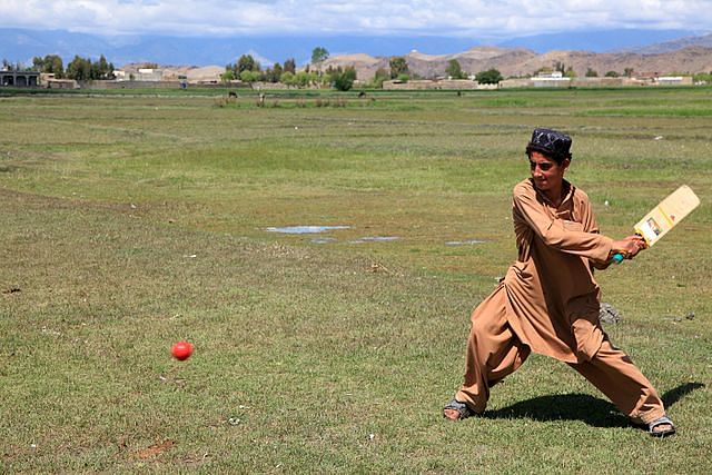 Young Afghan boy gearing up slog the ball for a six