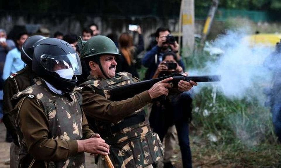 Policemen fire teargas during a stir by JMI students against the CAA in New Delhi.