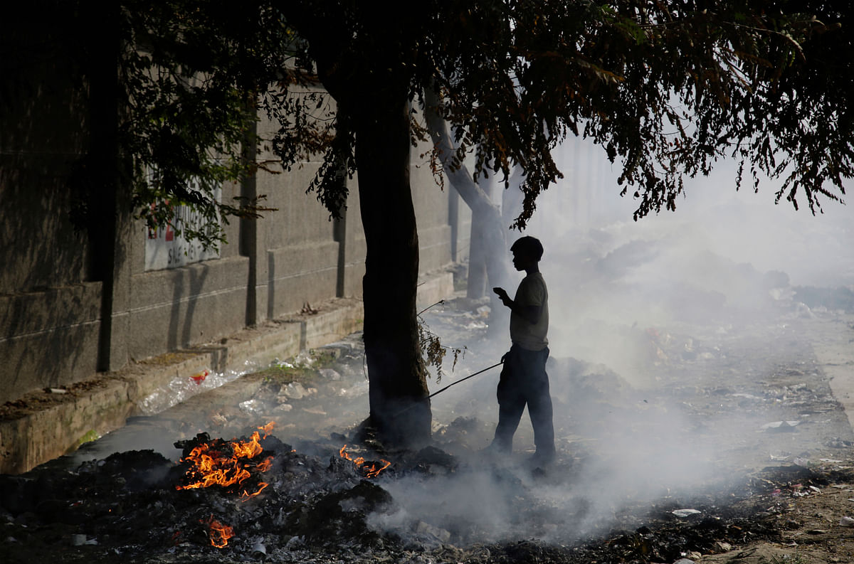 A ragpicker boy stand next to burning garbage on the outskirts of Delhi.