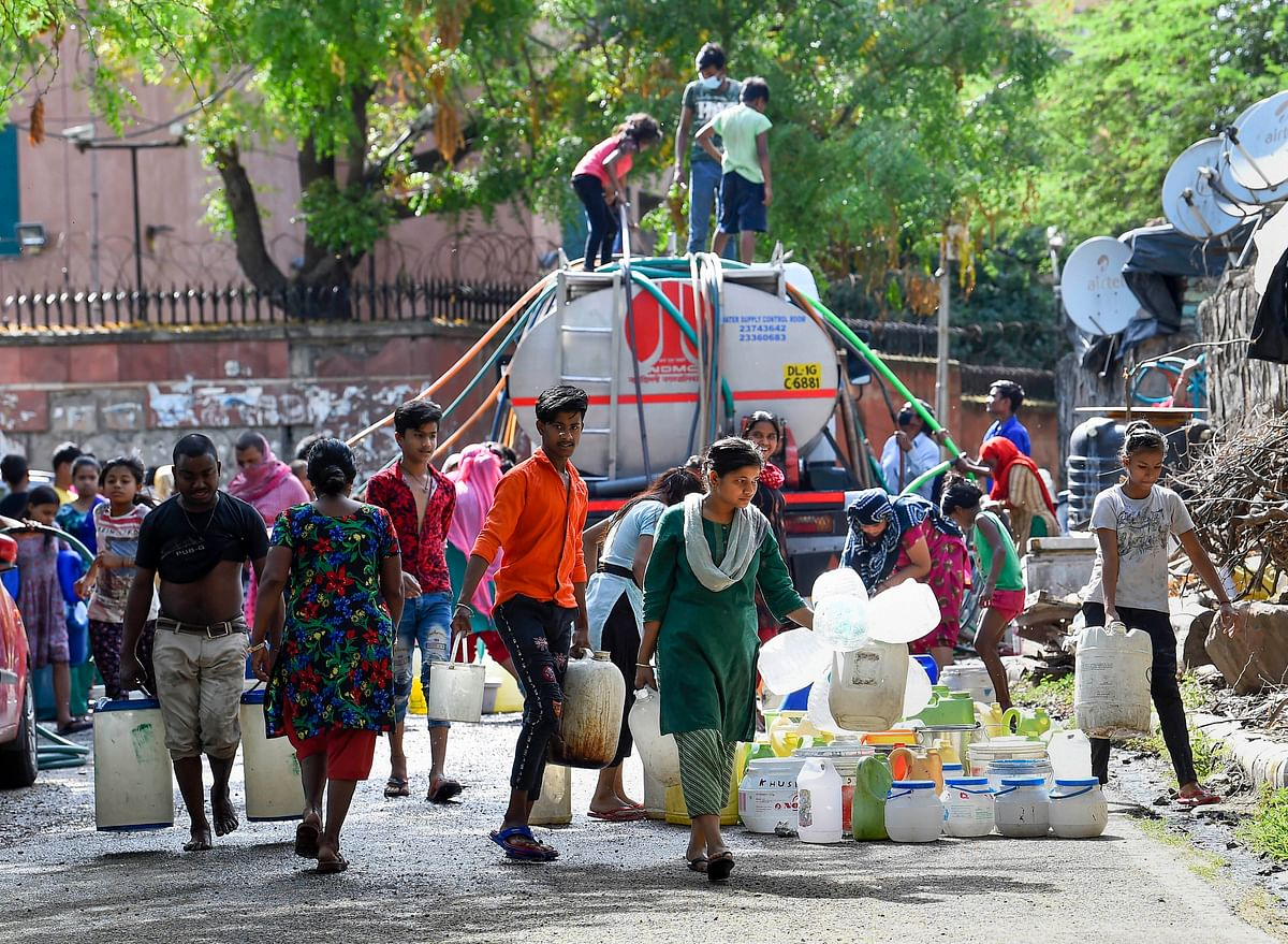 People collect drinking water from a tanker at Vivekanand Camp, Chanakyapuri without following social-distancing guidelines, during the ongoing COVID-19 lockdown in New Delhi on Friday, 17 April.