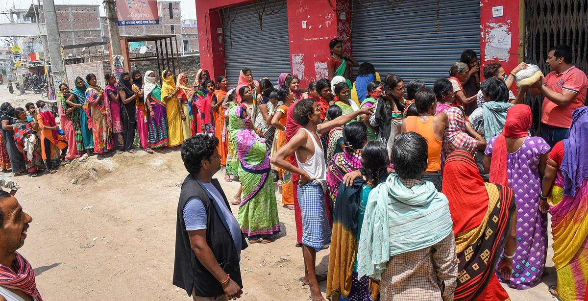 People stand in queues ignoring social distancing to collect essential food items by volunteers during the nationwide lockdown to curb the spread of coronavirus, in Patna on Saturday, 18 April.