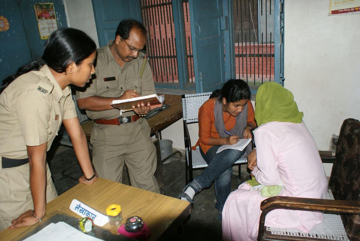 पुलिस स्टेशन में रिपोर्ट दर्ज कराती  महिला
