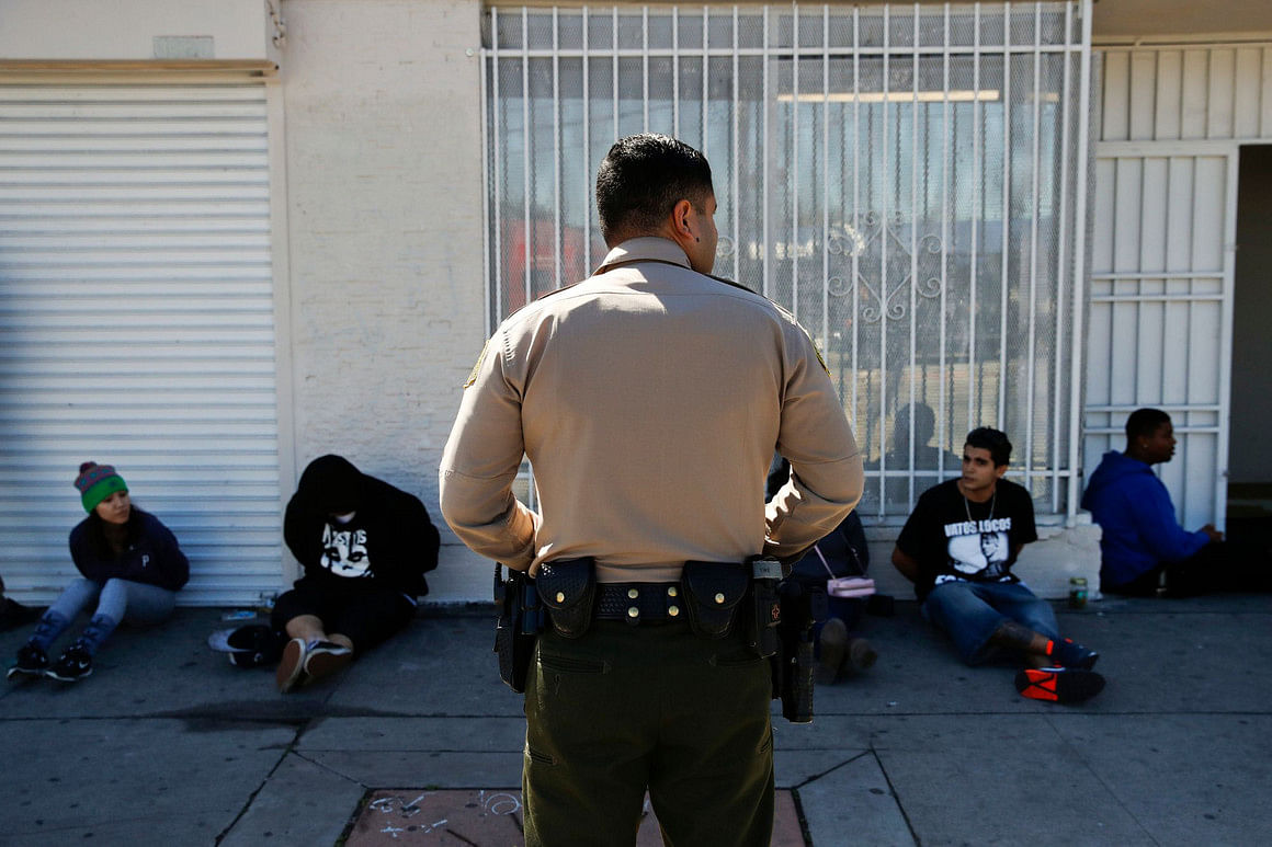 An officer keeps watch on a group of people apprehended at an illegal marijuana shop in Compton, Calif., in 2018