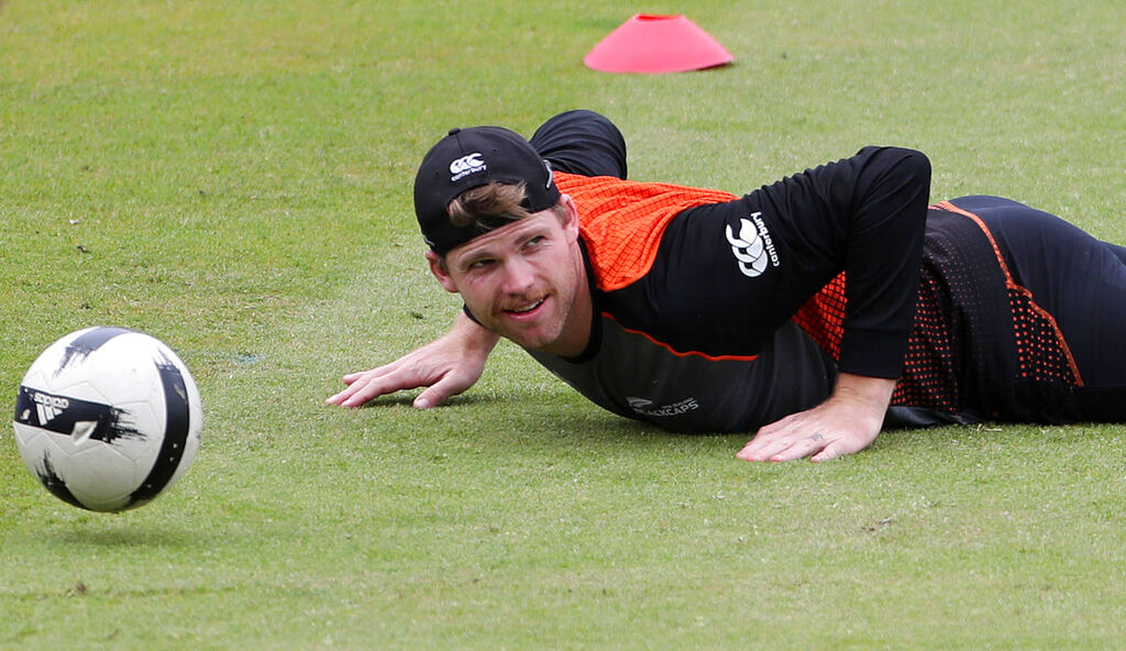 New Zealand's Lockie Ferguson falls on the ground while playing with a soccer ball during a training session ahead of their Cricket World Cup semifinal match against India at Old Trafford in Manchester.